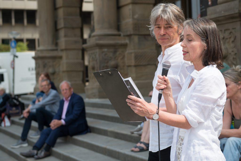 Christine Grunert und Olaf Herzog verlesen die Petition zur Unterstützung der Tango-Kulturschaffenden. Bürgermeister Pit Clausen hört zu.