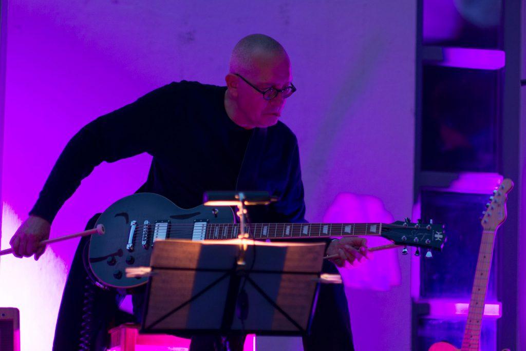 Musiker mit Gitarre bei schlechter Beleuchtung, Avantgarde-Spielhaltung mit Drumsticks